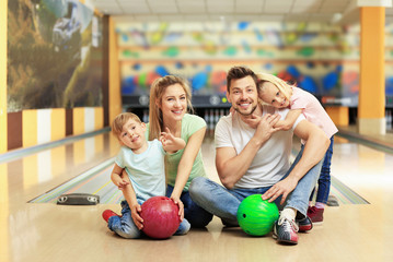 Happy family sitting on floor in bowling club
