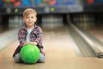Cute little boy with ball sitting on floor in bowling club