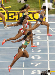 Carmelita Jeter of the U.S. lunges at the finish line ahead of her competitors winning the women's 100 metres final in Daegu