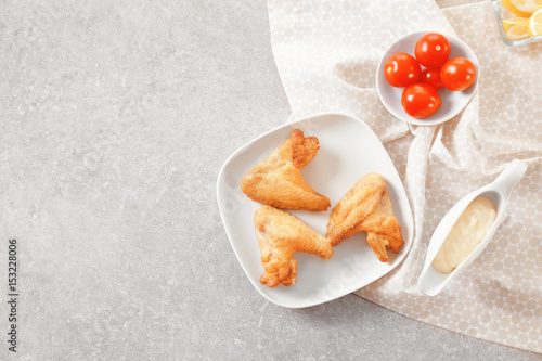 Composition With Chicken Wings And Tasty Mayonnaise Sauce On Kitchen Table