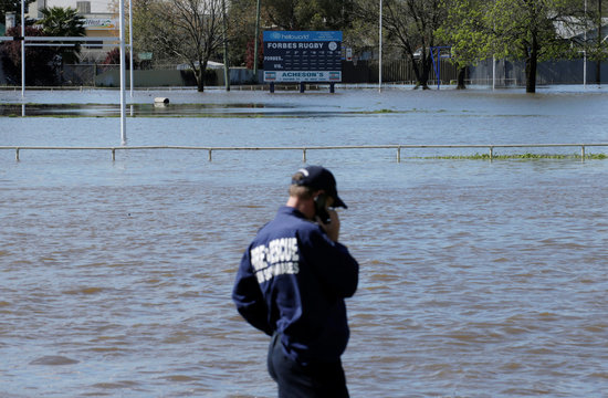 A New South Wales Fire and Rescue worker stands alongside a flooded lake which inundated a rugby field after heavy rain created a declared natural disaster zone in the midwestern New South Wales town of Forbes