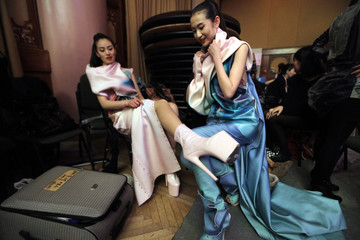 A model shows her high-heeled shoe backstage at China Fashion Week in Beijing