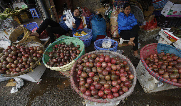 Fruit vendors sit behind baskets of passion fruit as they wait for customers at the Long Bien wholesale market in Hanoi