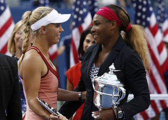 Williams of the U.S. and Wozniacki of Denmark chat as they hold their trophies after Williams won their women's singles finals match at the 2014 U.S. Open tennis tournament in New York