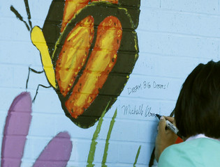 U.S. first lady Michelle Obama autographs her painting of a butterfly in Washington