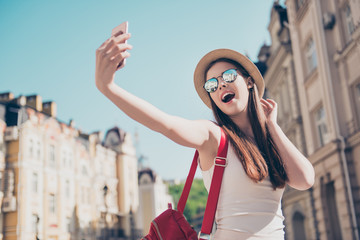Young attractive playful tourist is making selfie on the phone outside, wearing hat, sunglasses, light dress and red backpack