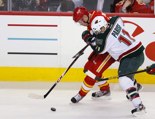 Minnesota Wild's Parise and Calgary Flames' Tanguay battle for the puck during their NHL hockey game in Calgary