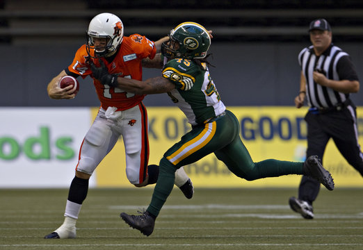 BC Lions quarterback Lulay is chased down by Edmonton Eskimos Munoz during CFL football game in Vancouver