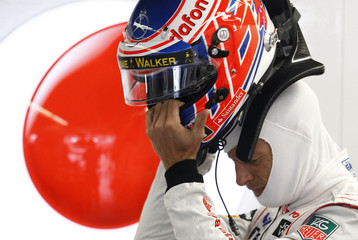 McLaren Formula One driver Button of Britain handles his helmet during second practice session of Canadian F1 Grand Prix at the Circuit Gilles Villeneuve in Montreal