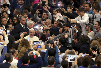 Pope Francis smiles as he arrives to lead a special audience with Catholic doctors at the Paul VI hall at the Vatican