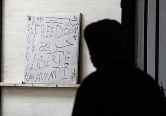A North African migrant walks past a poster which with the words 'Freedom' in English, Arabic, French and Italian at Ventimiglia train station, on the Franco-Italian border