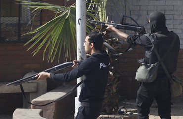Members of the police special forces fire rubber bullets during a demonstration at the front of Cairo University