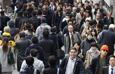 People walk along a street at Tokyo's Shinjuku shopping and business district