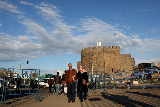 People, with the historical city walls in the background, leave from Sur district, which is partially under curfew, in the Kurdish-dominated southeastern city of Diyarbakir