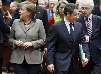 Germany's Chancellor Merkel and France's President Sarkozy arrive at an EU extraordinary leaders summit on Libya and North Africa in Brussels
