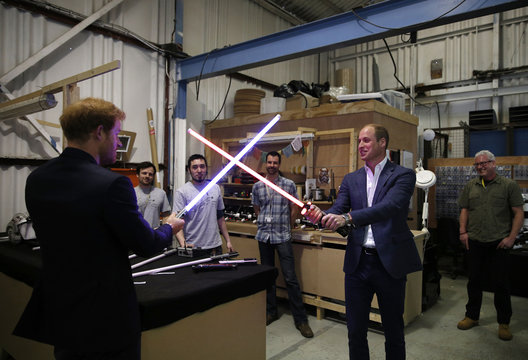 Britain's Prince William (R) tries a light sabre against his brother Prince Harry during a visit to the Star Wars film set at Pinewood Studios near Iver Heath, west of London