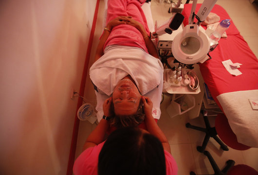 A man, wearing an anti-aging facial mask, receives a massage at a skin care clinic in a mall in Quezon City Metro Manila