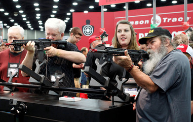 Gun enthusiasts test out laser sights at Crimson Trace Corp. at the National Rifle Association's annual meetings and exhibits show in Louisville