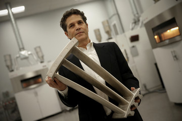 Bernard Plishtin, Chief Business Development Officer at Oxford Performance Materials, Inc., holds a 3-D printed exit guide vane for a jet engine in the Laser Melting Room at Oxford Performance Materials Inc., in South Windsor, Connecticut