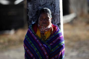 A woman from the Tarahumara ethnic group receives the heat of the sun on her face as they prepare for winter in Caborachi village