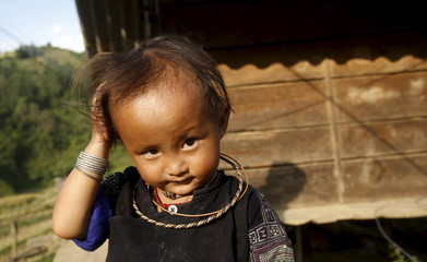 A Vietnamese girl of Hmong ethnic tribe wipes her head while waiting for return of her mother during the harvest season in Mu Cang Chai, northwest of Hanoi