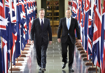 British Prime Minister David Cameron walks with Australian Prime Minister Tony Abbott from the House of Representatives at Parliament House in Canberra