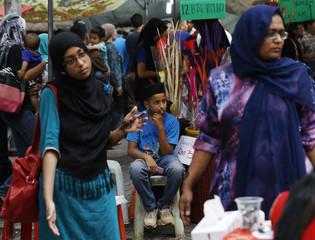 Women shop before Eid al-Fitr celebrations, which marks the end of Ramadan, as a boy looks on in Kuala Lumpur