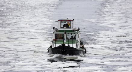 A vessel drives along the Spree river covered with ice floes in Berlin