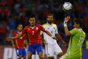 Chile's Sanchez and Venezuela's Vizcarrodo watch as Venezuela's goalkeeper Hernandez reaches for the ball during a friendly soccer match in Talcahuano