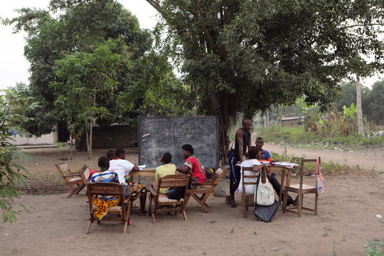 Students take a mathematics tutoring session under a tree in Bingerville