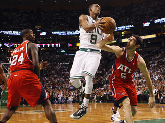 Boston Celtics' Rondo drives to the basket between Atlanta Hawks' Williams and Hinrich during their NBA Eastern Conference playoff basketball series in Boston