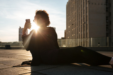 Curly african girl sitting outdoors on the roof taking mobile photos with sunset backlight over cityscape background