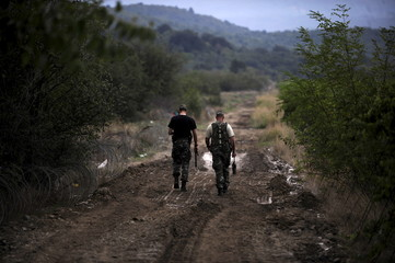 Macedonian soldiers walk at the border line with Greece near the transit camp in Gevgelija