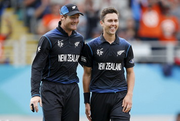 New Zealand's bowler Trent Boult celebrates with his team mate Martin Guptill after Boult bowled out South Africa's Hashim Amla during their Cricket World Cup semi final in Auckland