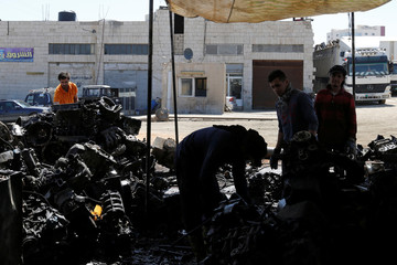 Jordanian graphic designer Abdelrahman Asfour, who turns car parts into furniture, looks through car parts at a junkyard in Amman