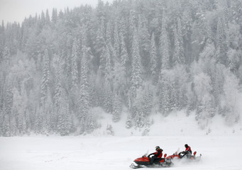 Participants compete during a snowmobile drag-racing competition on the ice-covered Mana River, south-east of Krasnoyarsk