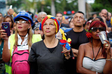 Opposition supporters participate in a candlelight rally against President Nicolas Maduro in Caracas