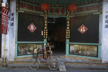 A man sits in front of a traditional medical shop in Vietnam's central ancient town of Hoi An, a UNESCO heritage site