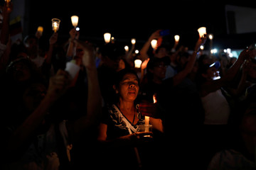 Opposition supporters hold candles while participating in a candlelight rally against President Nicolas Maduro in Caracas