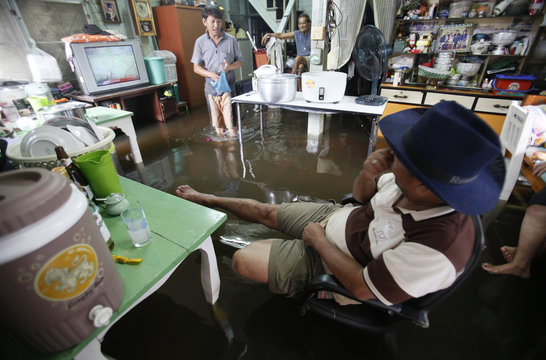 A family watches television in their flooded living room at Bang Phlad district, Bangkok