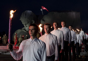 Participants hold torches during a commemorative ceremony at the Brest Hero Fortress memorial complex in the western city of Brest, Belarus