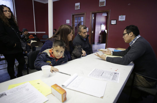 Attorney John Antia talks to migrant family attending a workshop for legal advice held by the Familia Latina Unida and Centro Sin Fronteras at Lincoln United Methodist Church in south Chicago