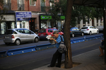 A man reads the newspaper as he waits for the bus in Madrid