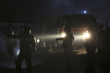 """French CRS riot police secure the area so firemen can arrive to extinguish fires on the second day of the evacuation and dismantlement of the camp called the """"Jungle"""" in Calais"""