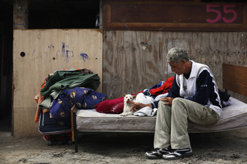 "Placintario caresses puppy as he sits next to belongings he salvaged before shack was demolished in shanty town settlement of ""El Gallinero"", in Madrid"