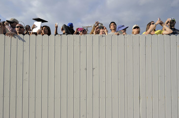 People take pictures behind a fence as Space Shuttle Endeavour is transported from Westchester Square to Randy's Donuts in Los Angeles, California