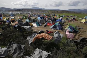 Migrants wait to cross the Greek-Macedonian border, at a makeshift camp near the village of Idomeni