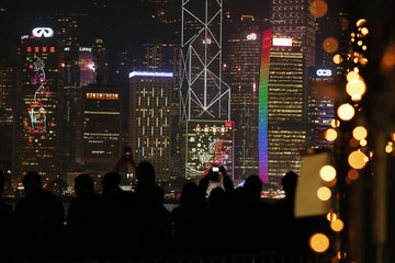Visitors take photos of the skyline of the financial Central district, featuring Chinese New Year decorations on the facades of commercial towers in Hong Kong