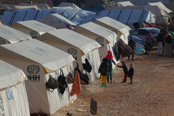 Evacuees from a rebel-held area of Aleppo, stand near their tents in al-Kamouneh camp, Idlib province