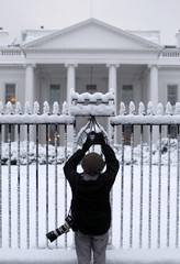 A photographer takes pictures of the snow at the White House in Washington